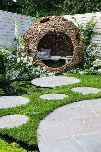 Un nido da giardino di rattan intrecciato, arredato con comode sedute.