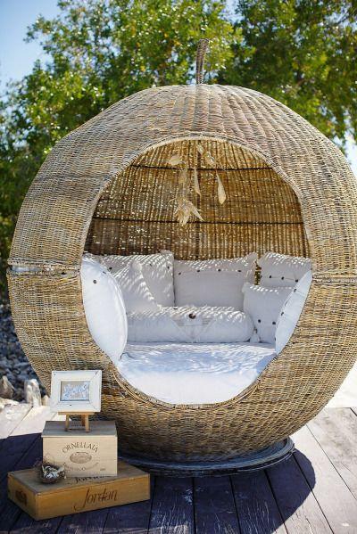 Sfera di bambù da giardino con comodi cuscini bianchi.