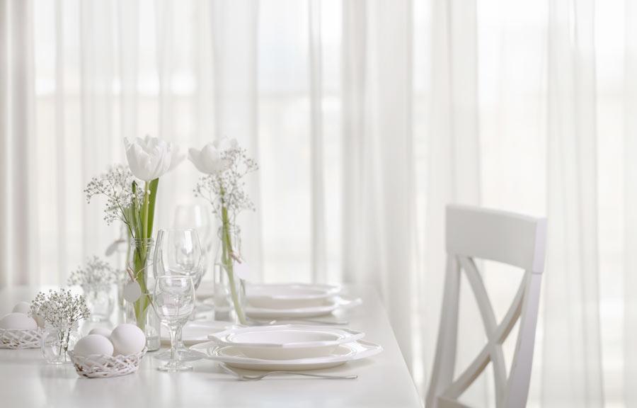 Tavola di Pasqua stile shabby chic, bianca con centrotavola floreale.