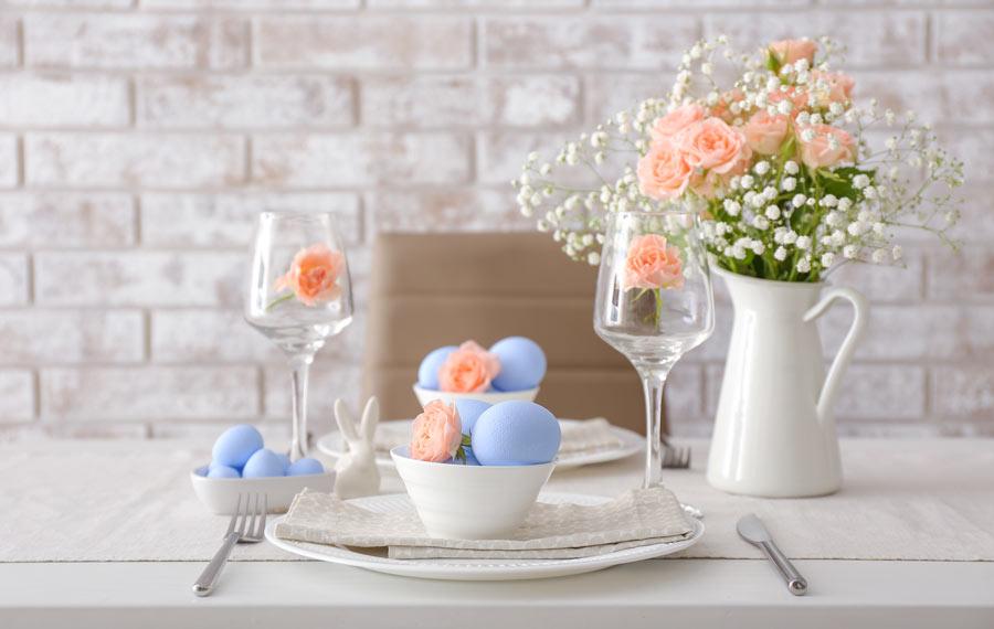 Tavola pasquale con ciotole bianche e ovetti celesti, vaso di fiori bianchi e rose.