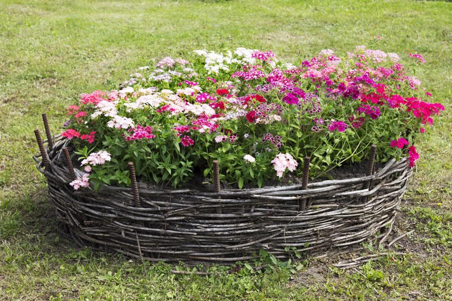 Grande vaso di fiori in vimini collocato in giardino.