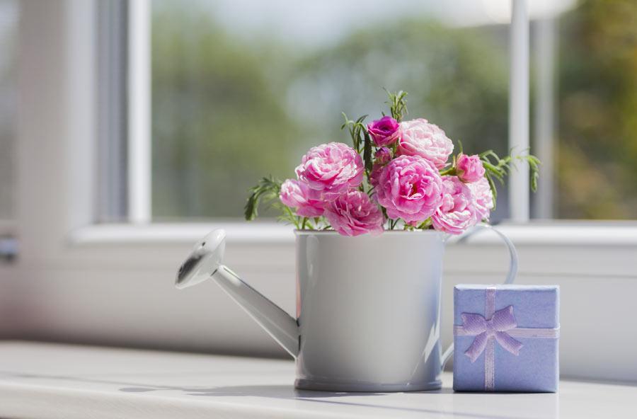 Innaffiatoio bianco decorato con delle rose.