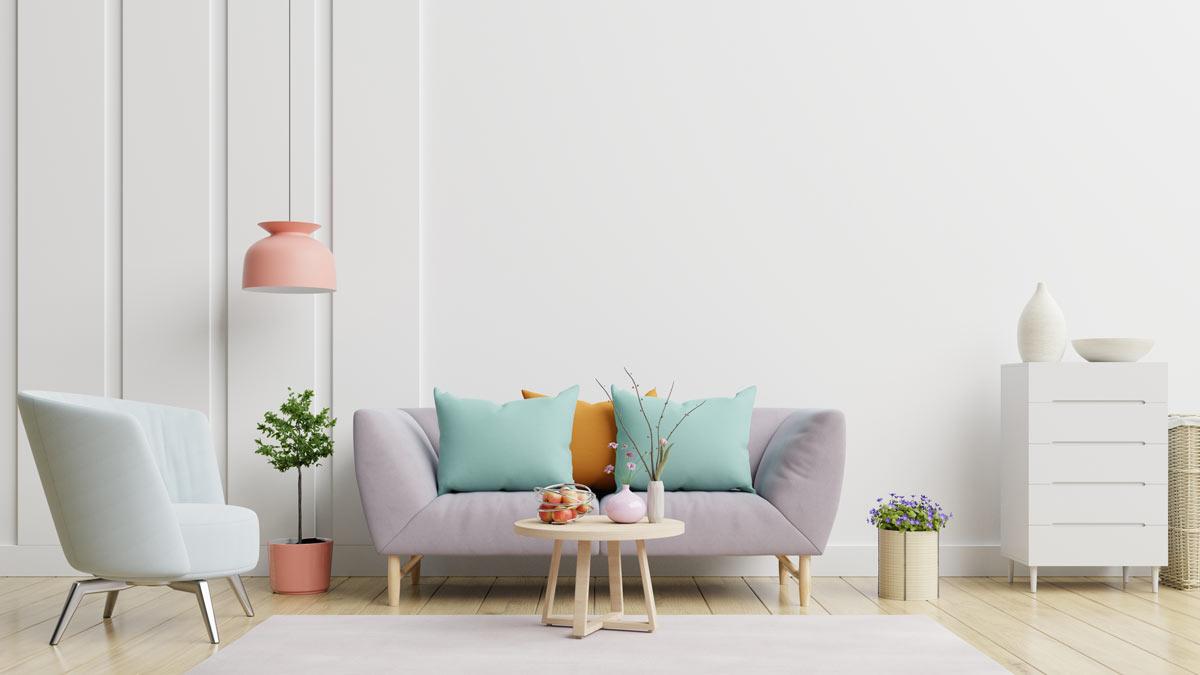 Piccolo divano 2 posti color lilla con dei cuscini decorativi color pastello.