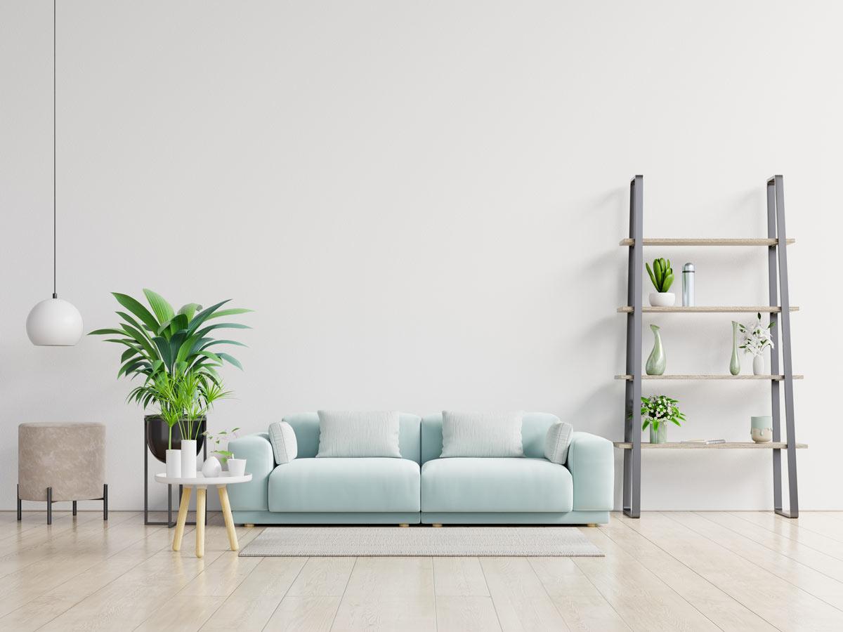 Salotto moderno con parete bianca e divano 2 posti color pastello celeste.