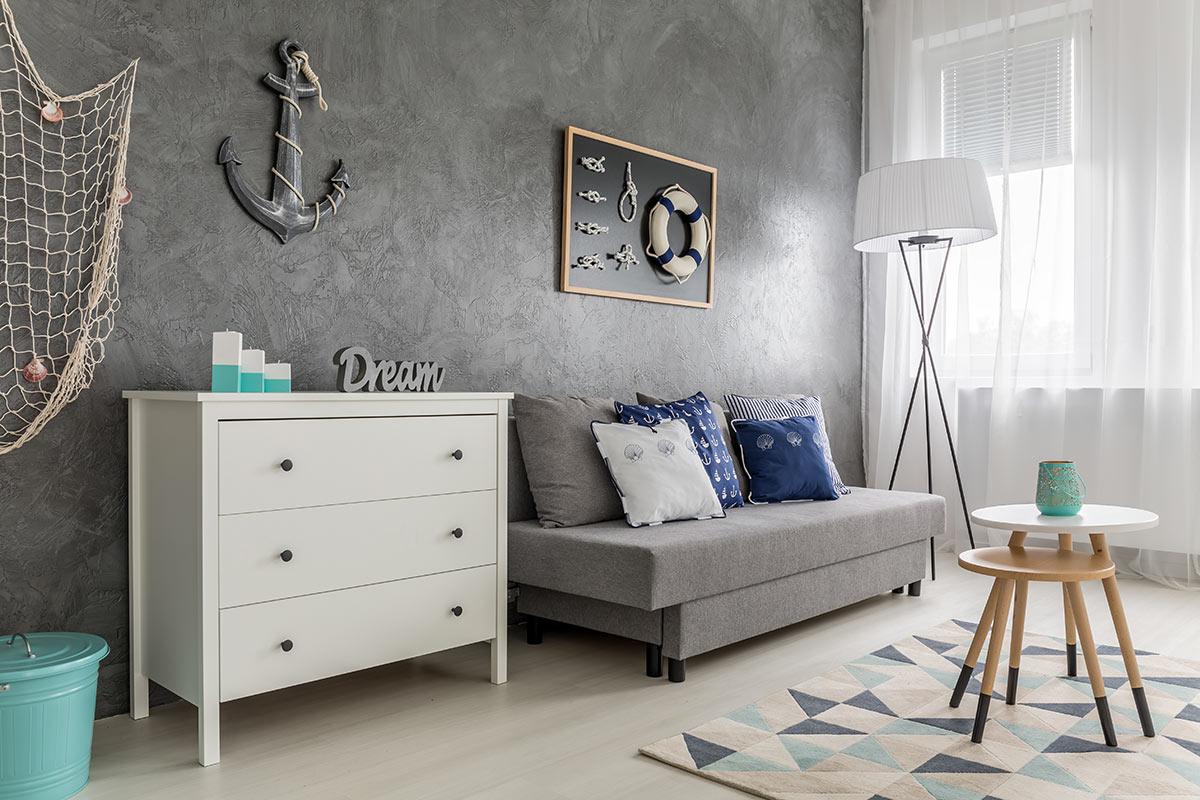 Salotto con parquet chiaro e parete grigia arredato nello stile marino.