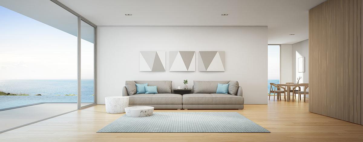 Grande salotto con divano tortora chiaro e cucini e tappeto celeste stile marino.