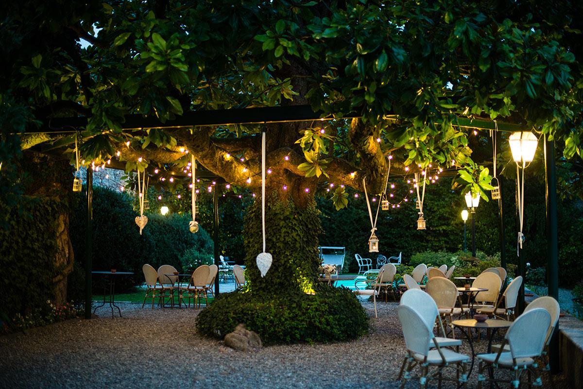 Terrazzo con Grande albero ombreggiante decorato con lucette di sera.