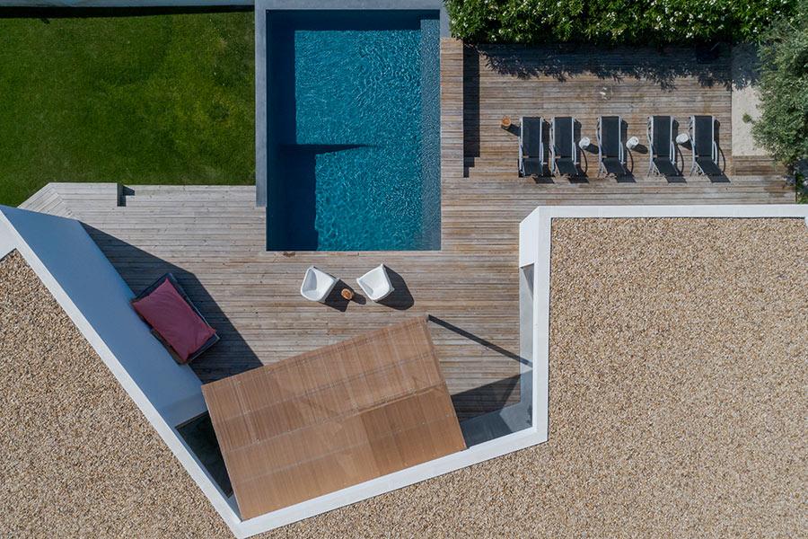 Terrazzo in legno con piscina fuori terra.