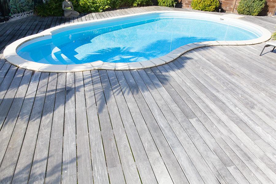 Pavimento in legno attorno piscina a forma libera.