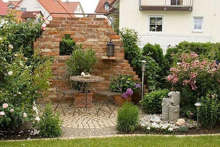 piccolo rudere in giardino con tavolino e sedie in ferro.