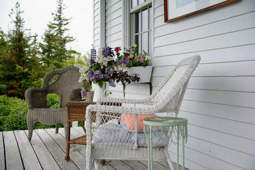 Terrazzo shabby con set divano e tavolo in vimini.