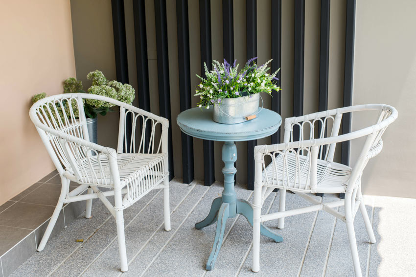 Piccolo terrazzo arredato in stile shabby chic con sedie bianche di vimini e tavolino rotondo celeste effetto invecchiato.