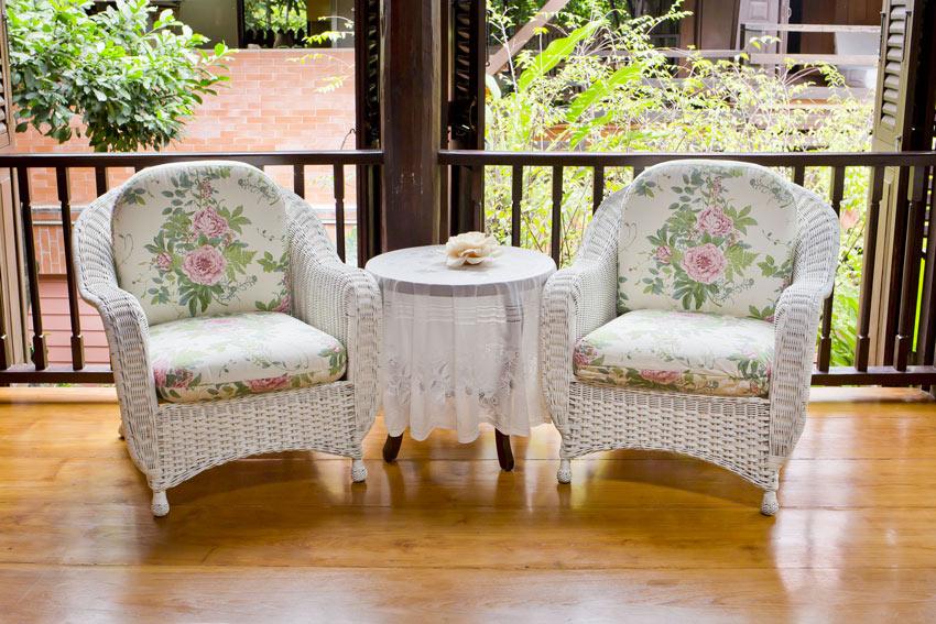 Salottino da esterno in vimini con cuscini con motivi floreali.