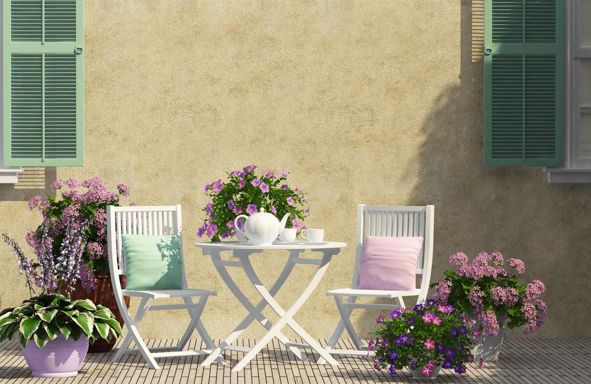 Terrazzo stile shabby con tavolino e sedie bianche con cuscini verde e rosa pastello.