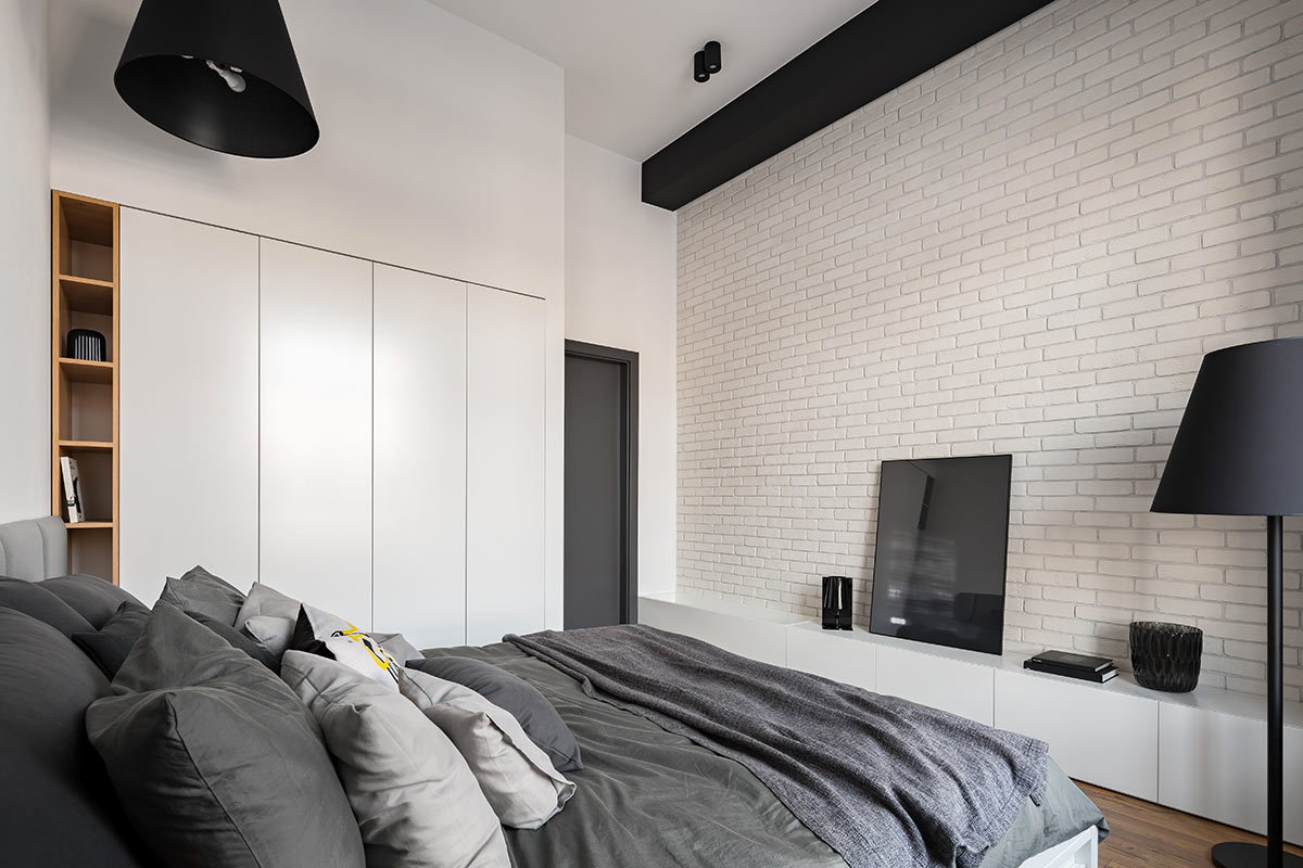 Camera da letto moderna con armadio a muro bianco su parete bianca.