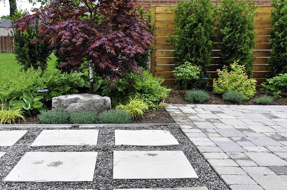Vialetto giardino con sassolini e lastre di pietre quadrate.