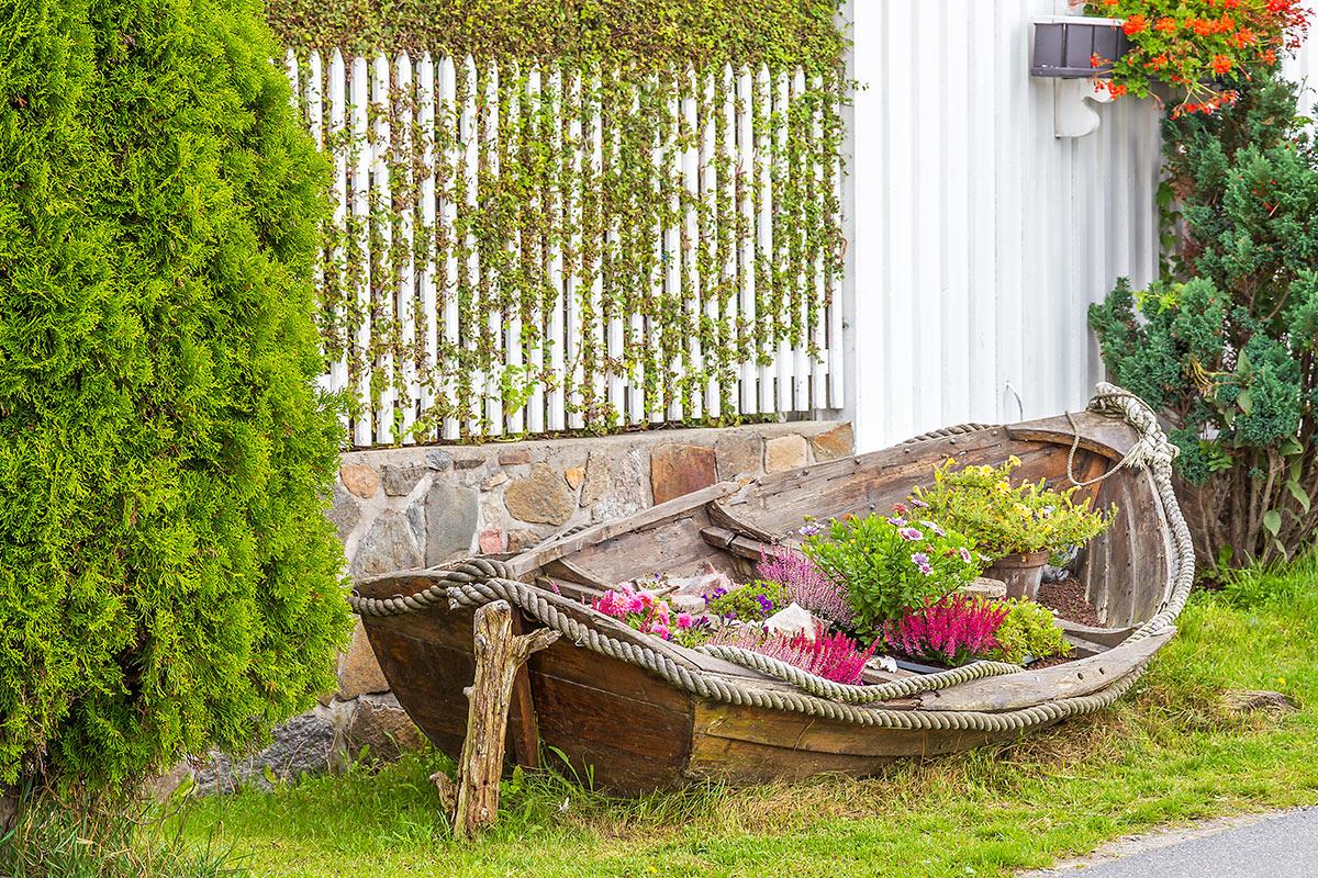 Vecchia barca decorata in giardino con dei fiori.