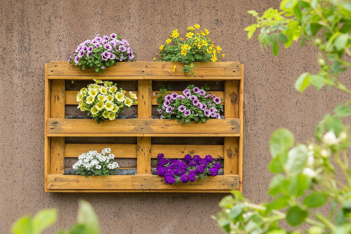 Pallet riciclato diventa bella fioriera in giardino.