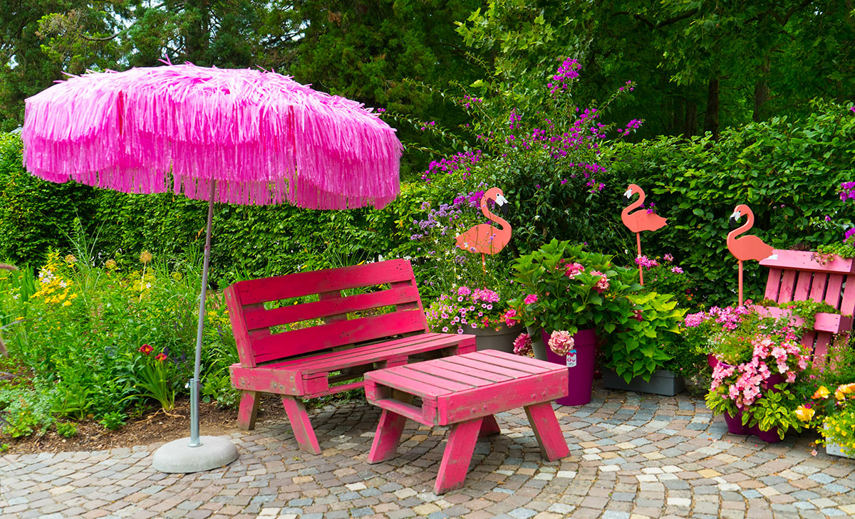 Panchina rosa da esterno con tavolino realizzato con i pallet.