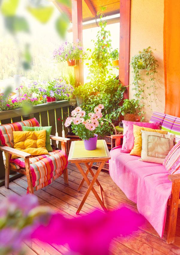 Zona relax su balcone pieno di fiori.