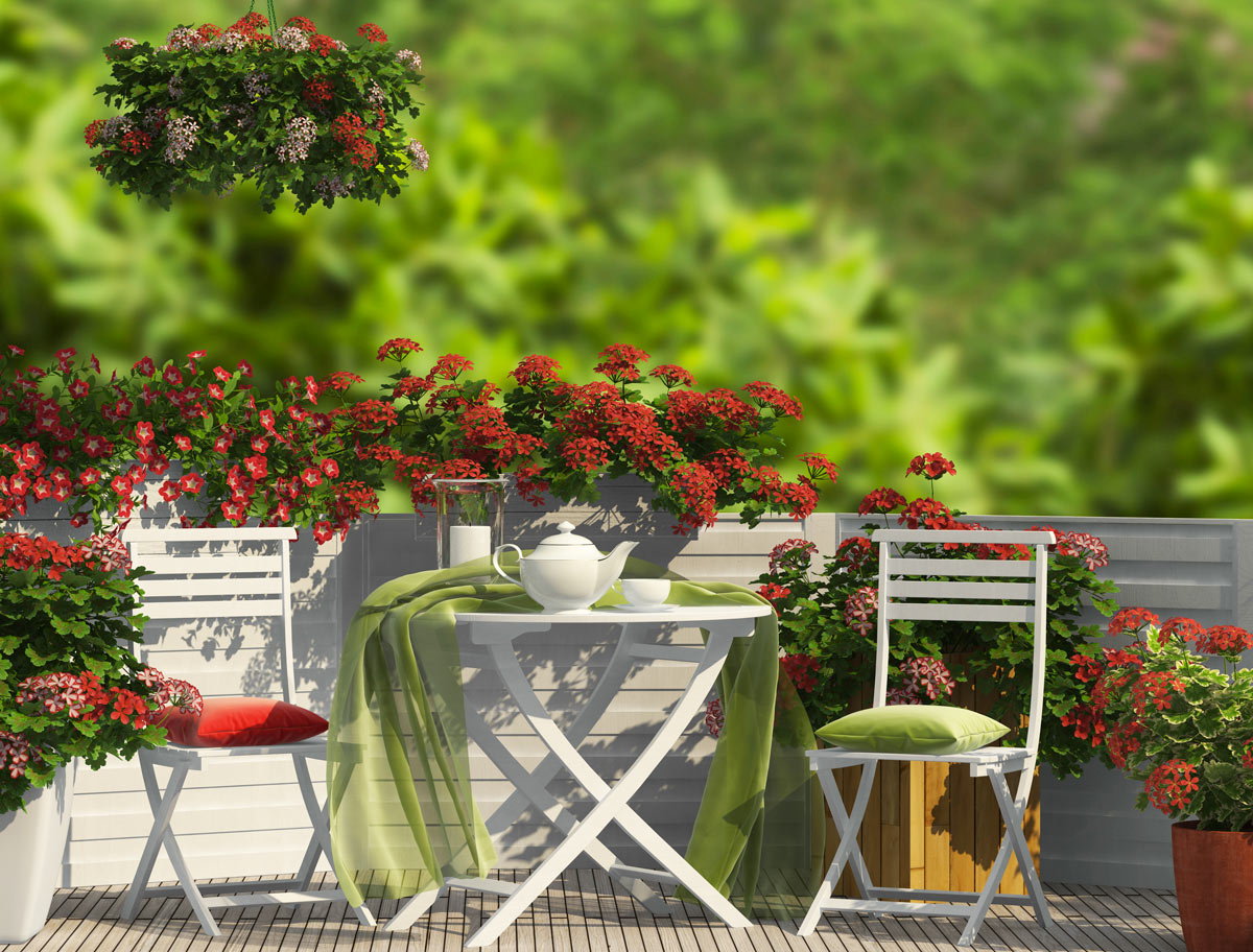 Balcone pieno di fiori con tavolino e sedie bianche.