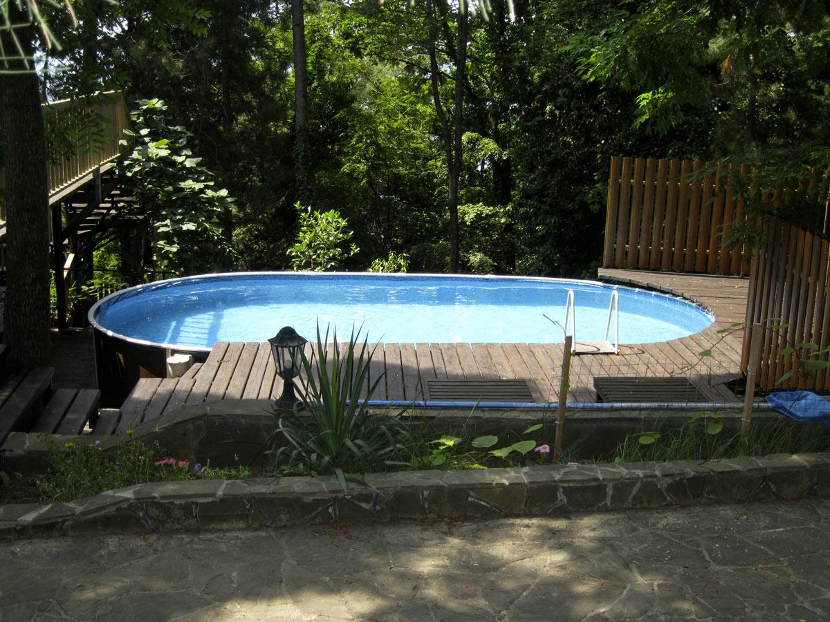 Grande piscina fuori terra ovale con soppalco in legno.