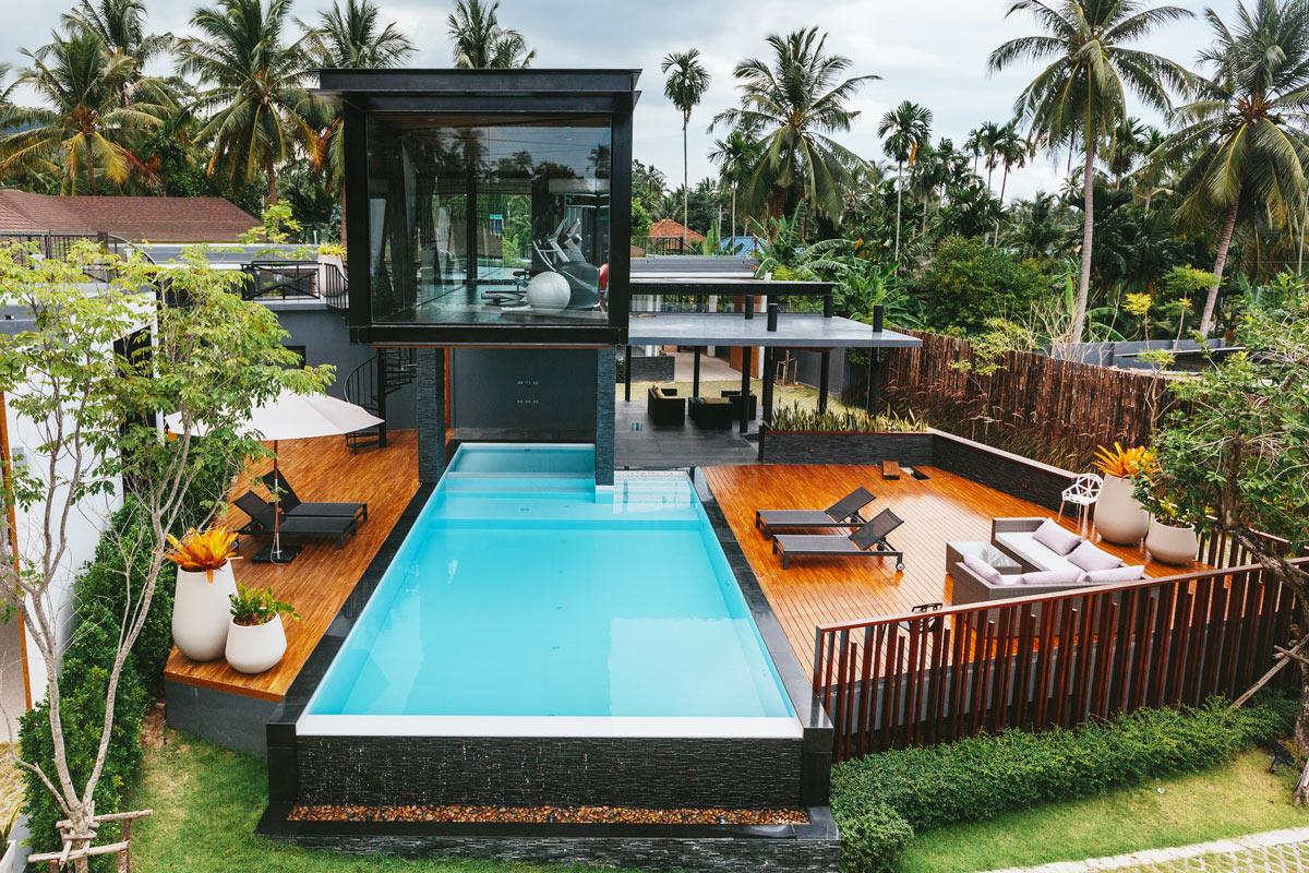 Bella piscina in casa con soppalco in legno, lettini neri con zona salotto esterno, divani con cuscini da giardino.