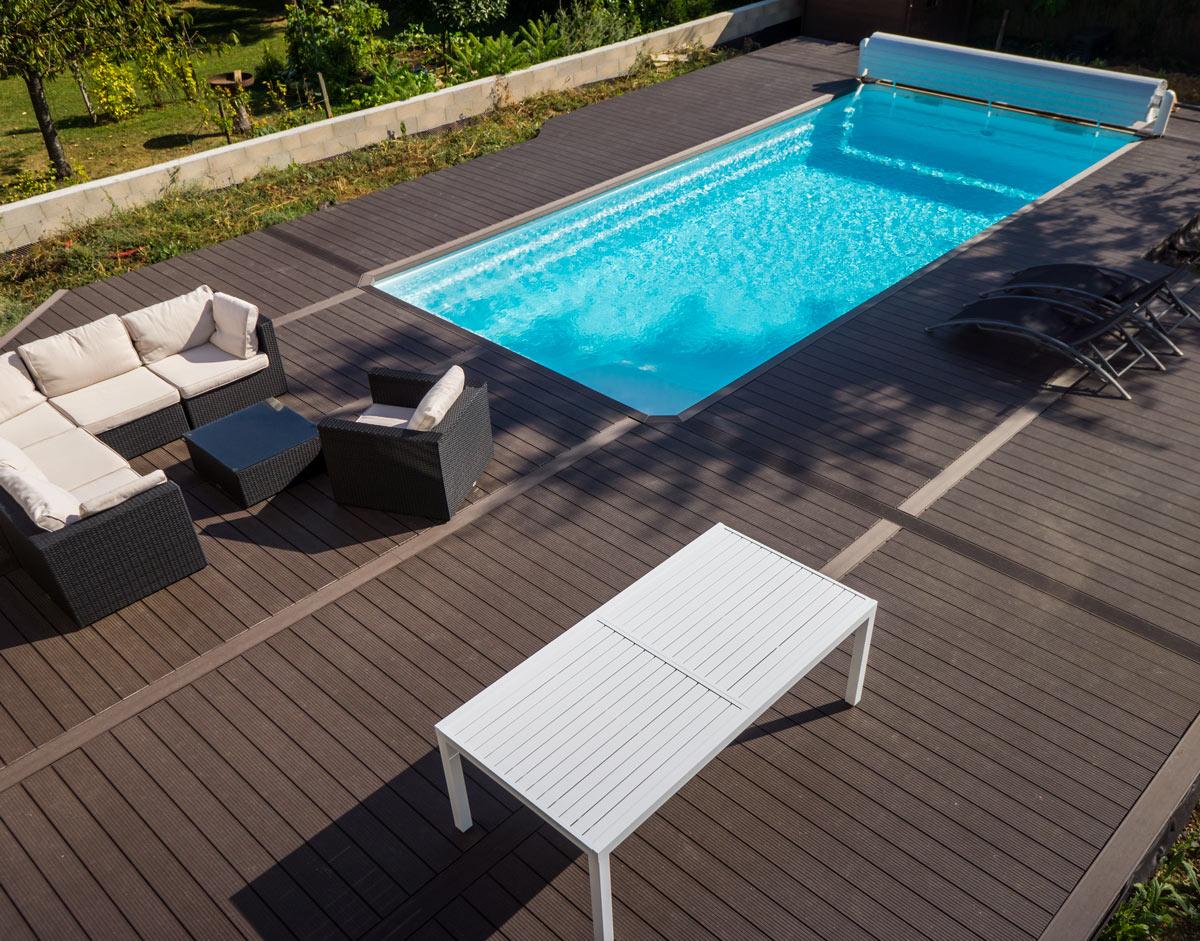 Piscina in casa con chiusura invernale, terrazzo con salotto da esterno, divani e poltrone da giardino.