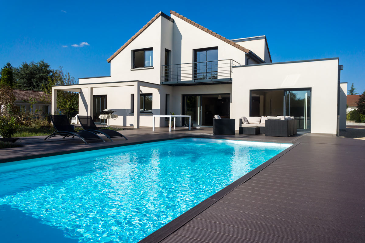 Bella casa con piscina rettangolare. Bordo piscina in legno scuro.