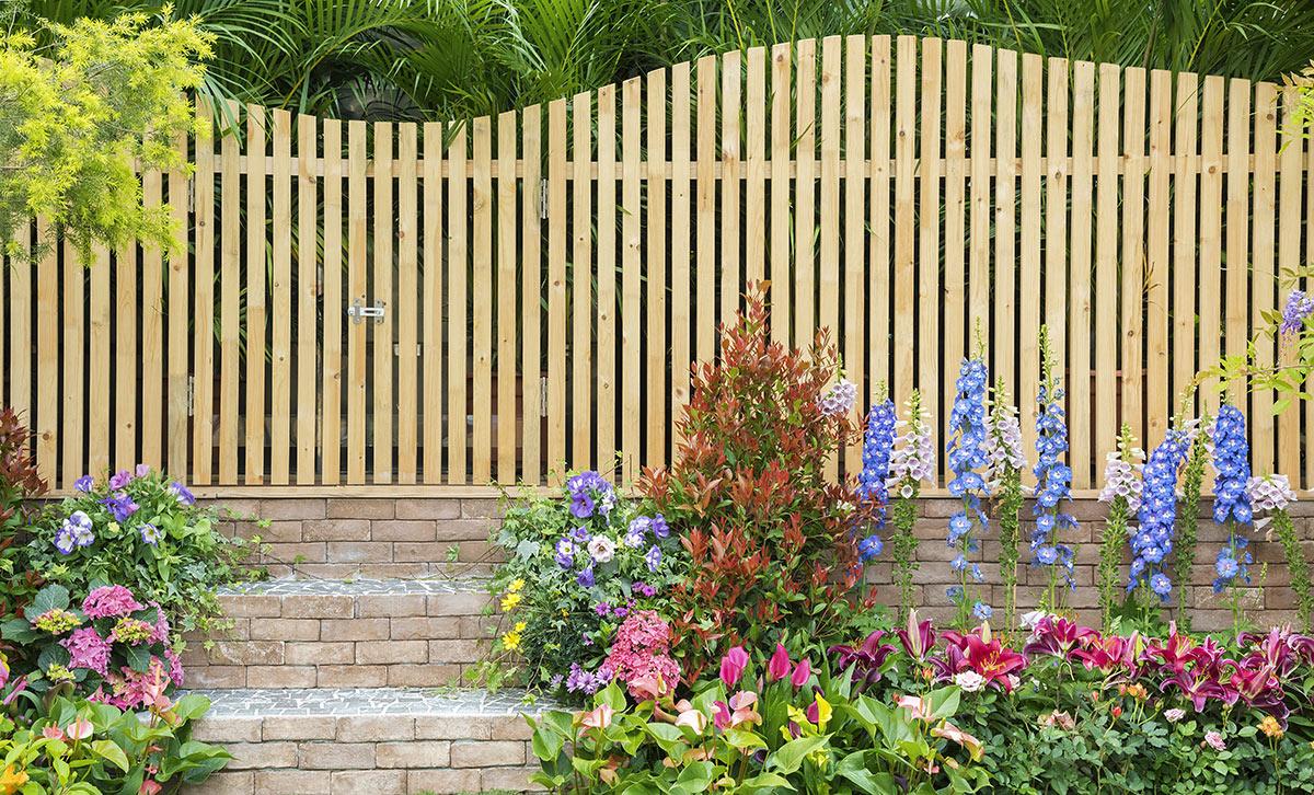 Bellissimo recinto in legno design, bei fiori colorati per decorare il giardino.