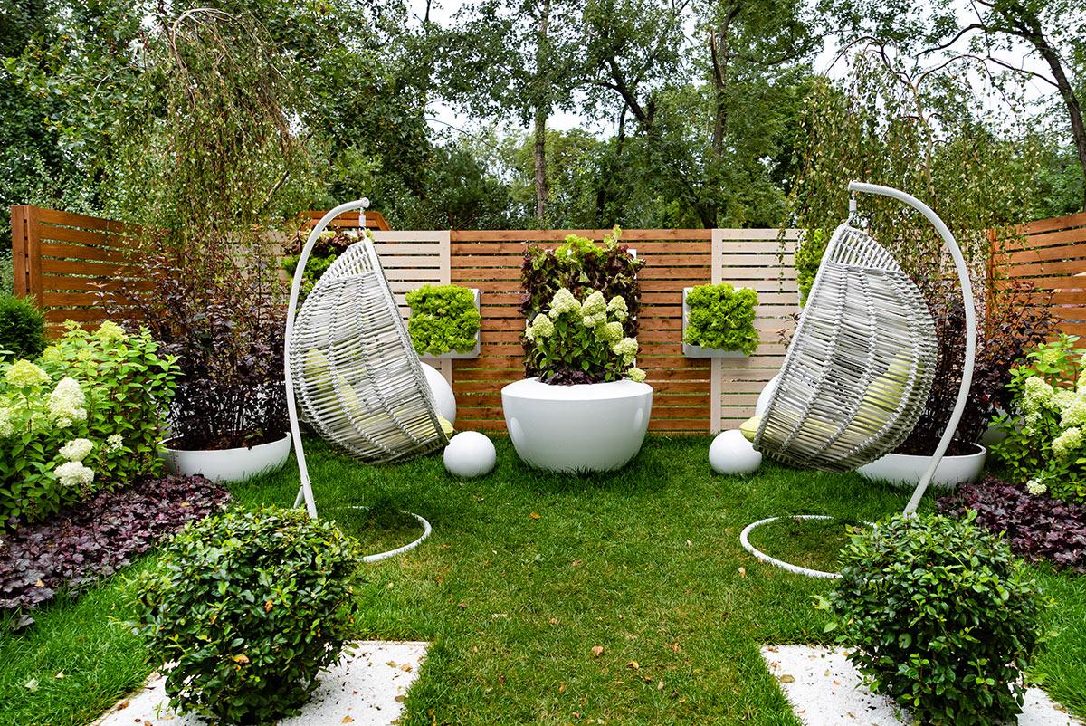 Piccolo giardino con recinto in legno, 2 poltrone da giardino a dondolo e decorazioni con piante.