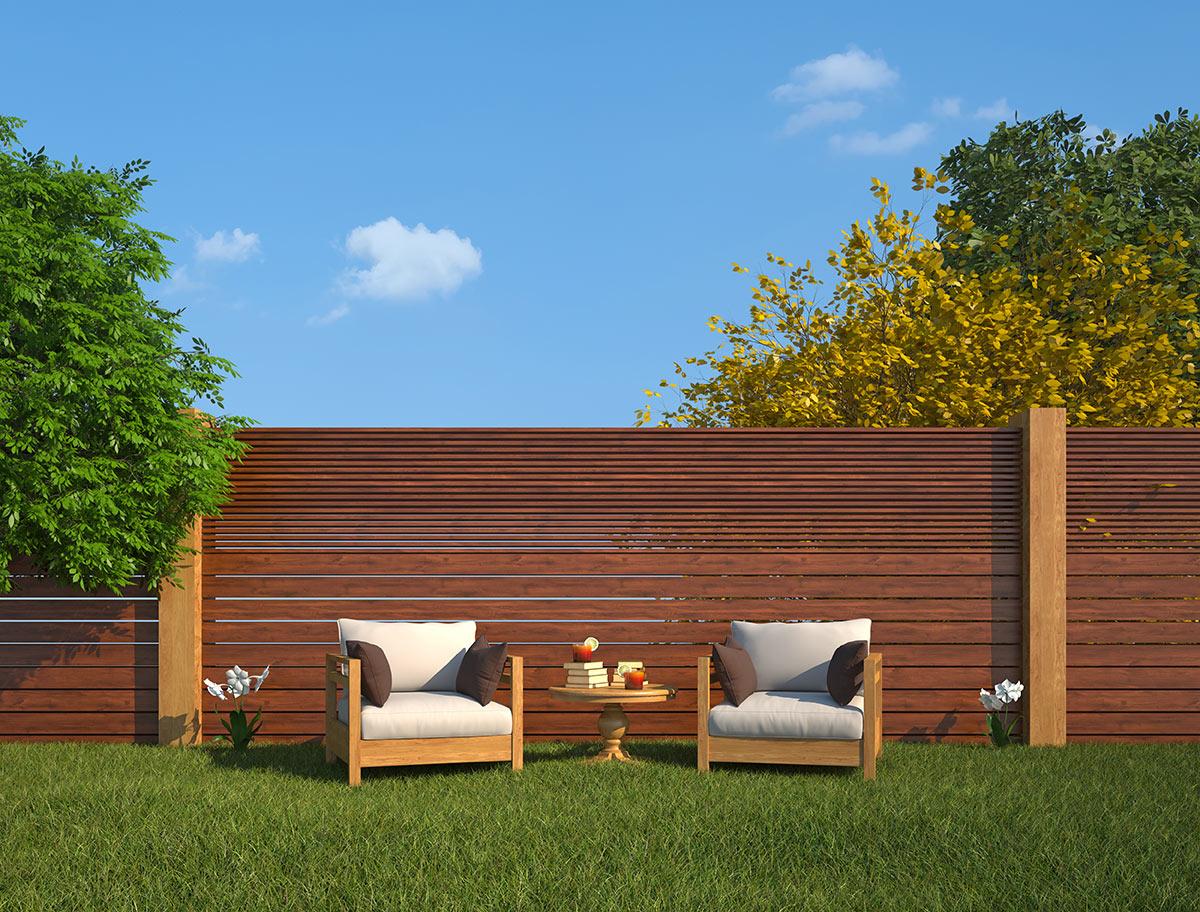 Grande recinto in legno con tavole in orizzontale, 2 poltrone da giardino con tavolino.