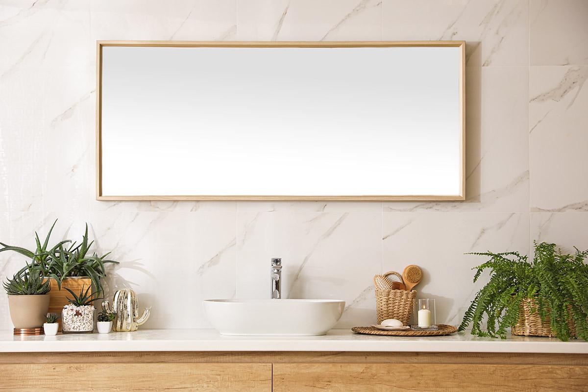 Specchio da bagno rettangolare con cornice in legno chiaro.