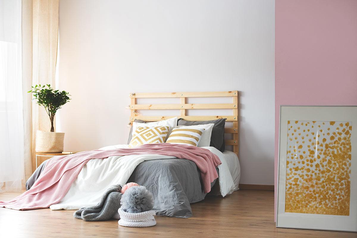 Testiera letto fai da te con bancali in questa camera con parete bianca e rosa.
