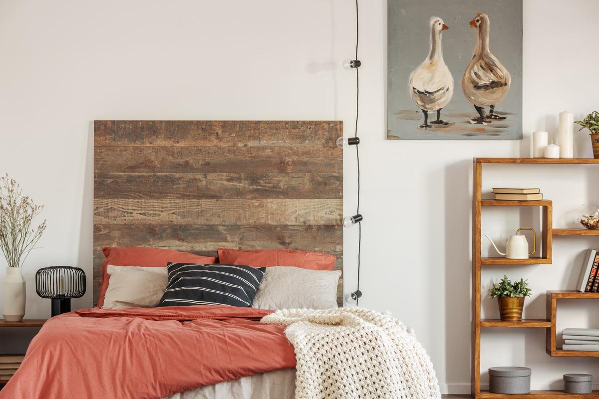 Camera arredata in stile moderno con testata letto fai da te realizzata con bancali.