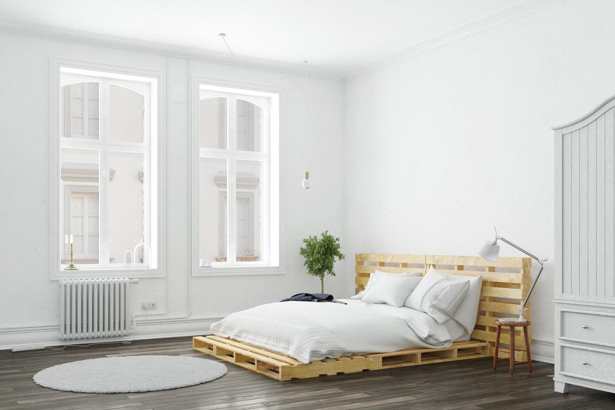 Camera bianca con letto realizzato in pallet di legno.