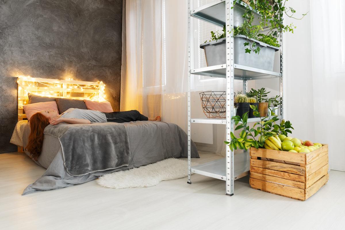 Testiera letto fai da te con bancali con lucette decorative.