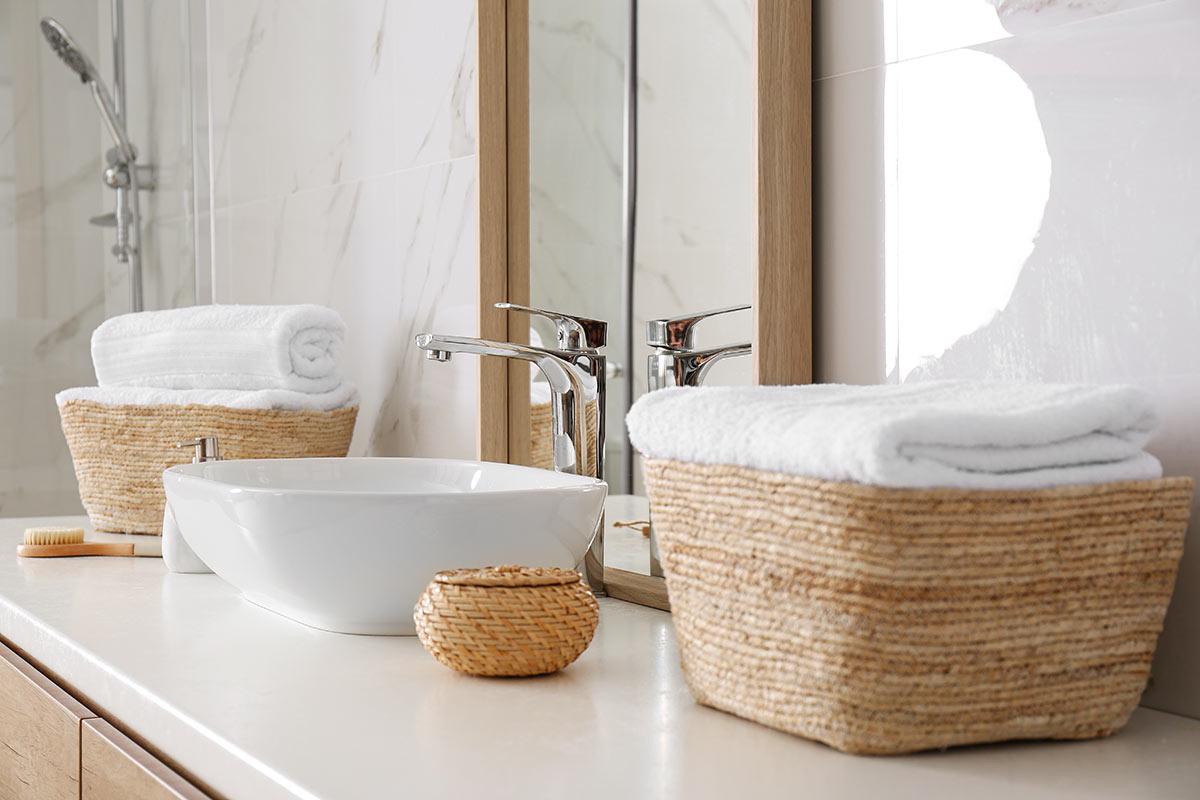 Sistemare il bagno con dei cestini in vimini.