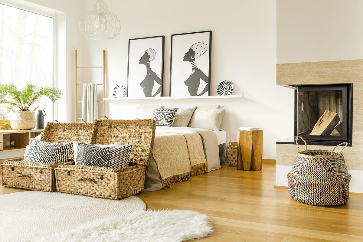 Camera da letto moderna con cenni africani e due bellissimi bauli in vimini ai piedi del letto.
