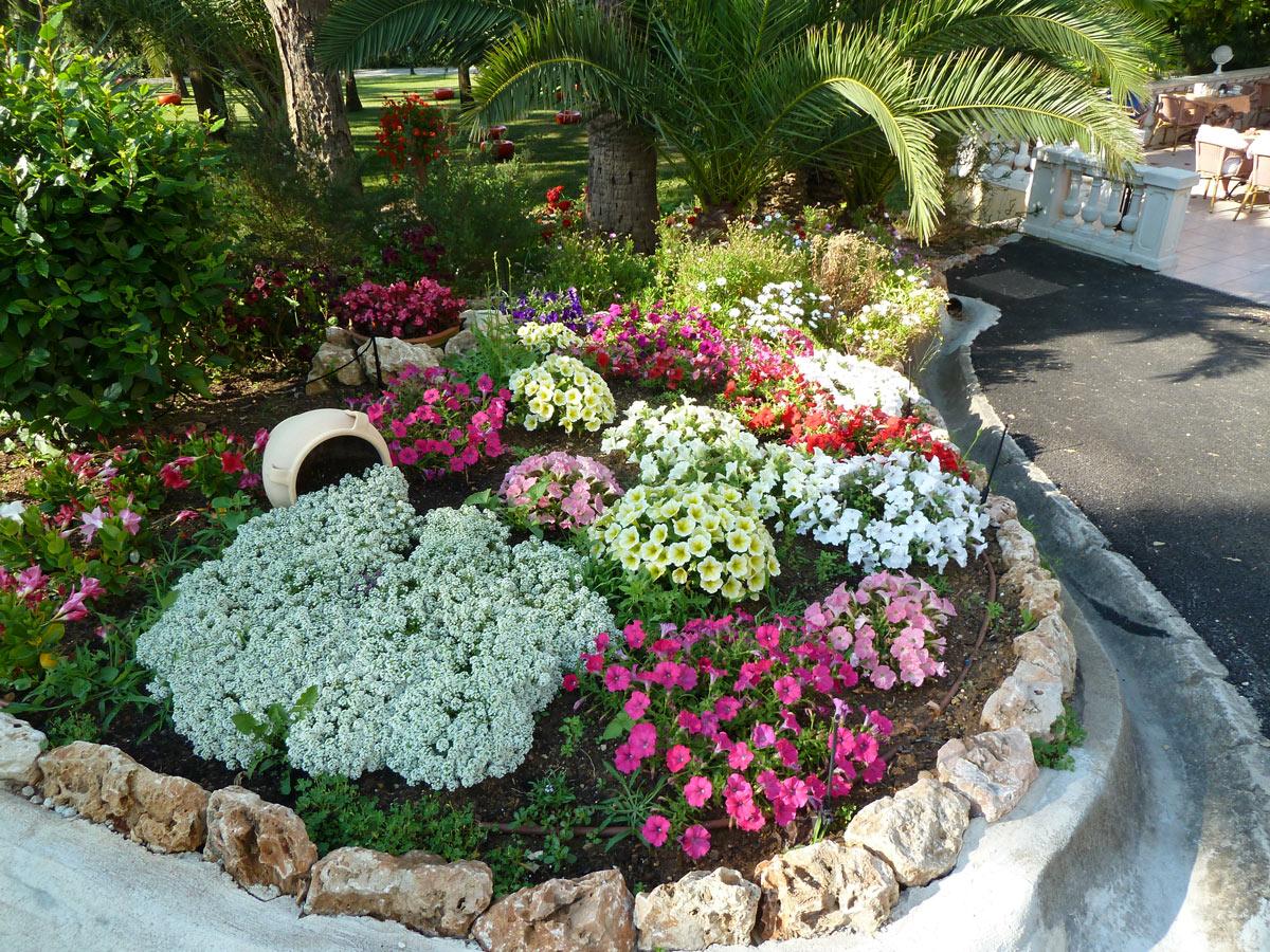 Splendida aiuola con bordi in pietra naturale, fiori colorati.