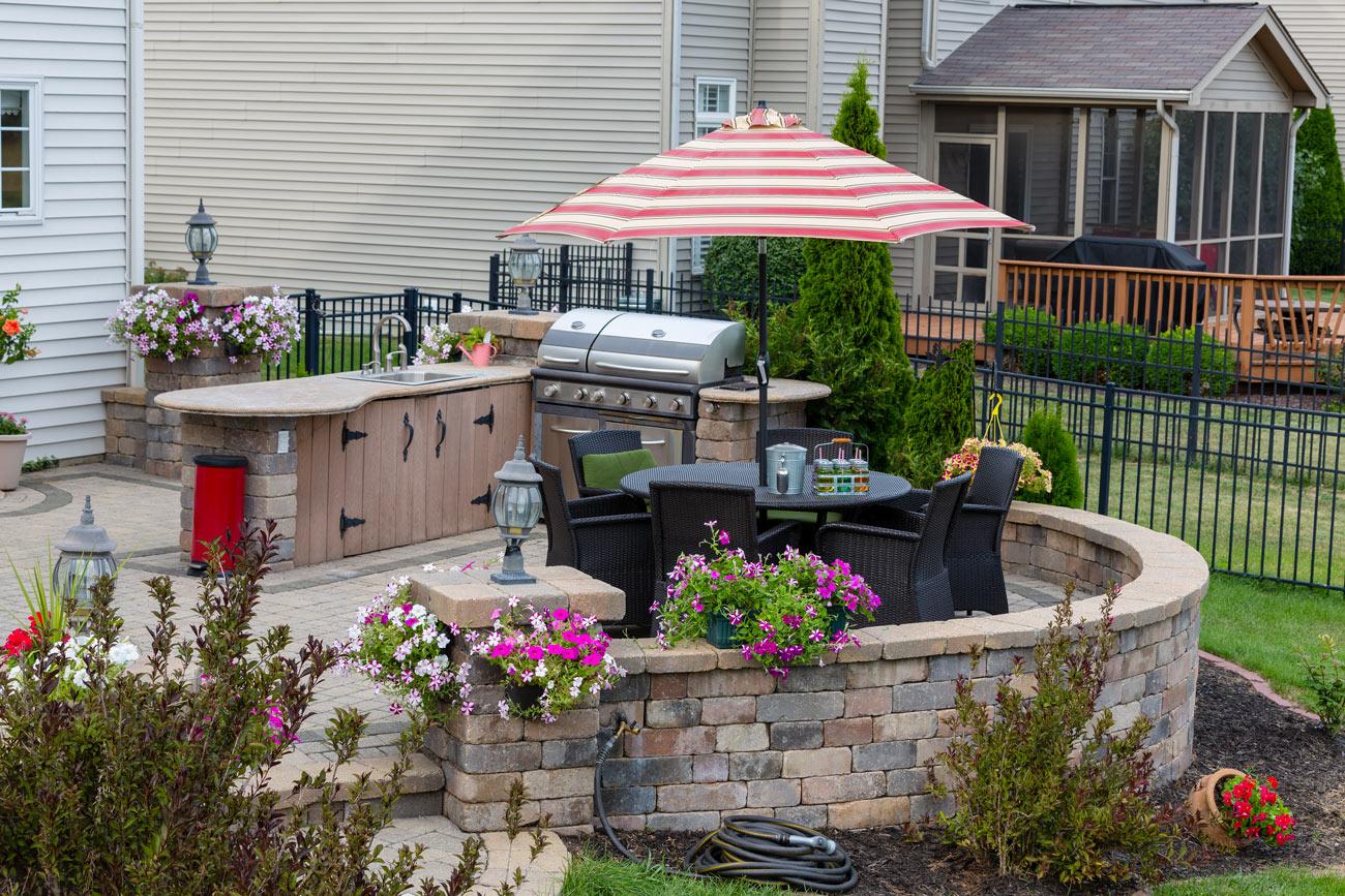 Cucina in giardino con lavandino e barbecue.