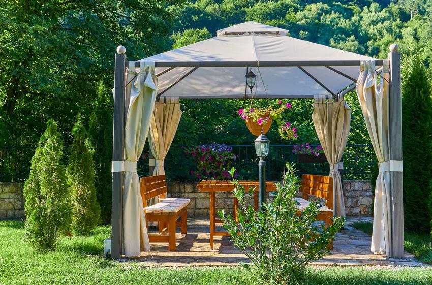 Tavolino con sedie in giardino all'ombra sotto un gazebo.