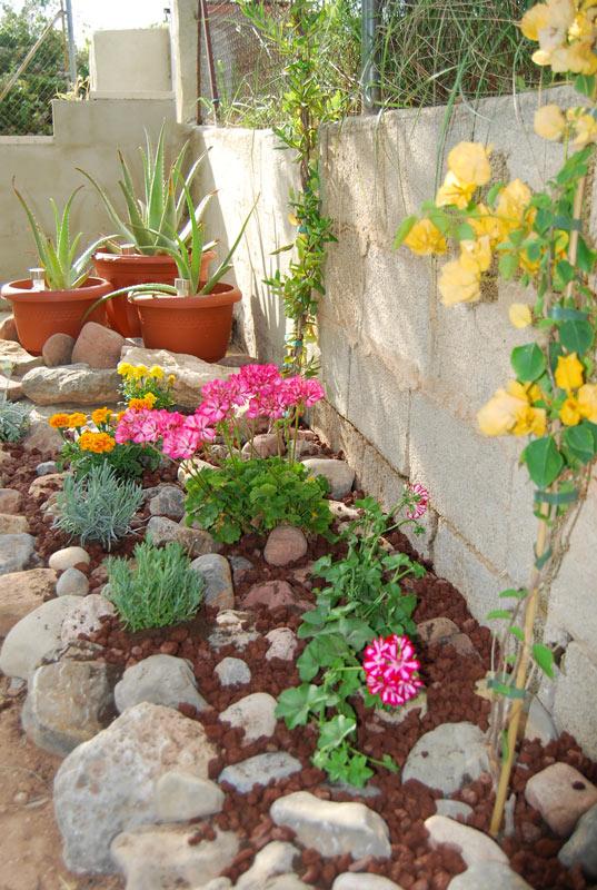 Aiuola vicino muro in lunghezza realizzata con sassi naturali e fiori.
