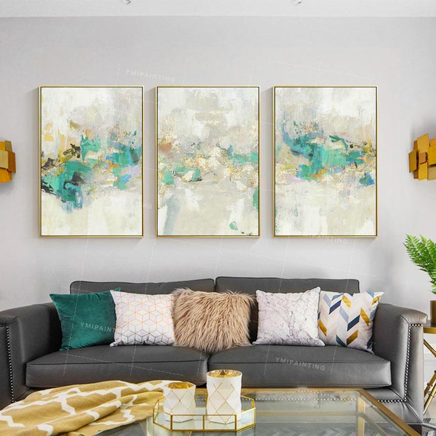 Tre quadri moderni astratti con cornice color oro sopra al divano in salotto.