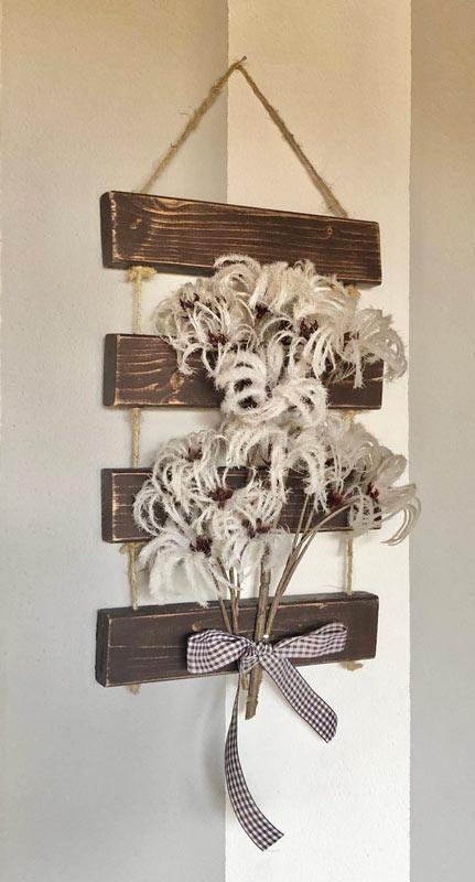 Decorazione fai da te da parete stile rustico con pallet e fiori secchi.