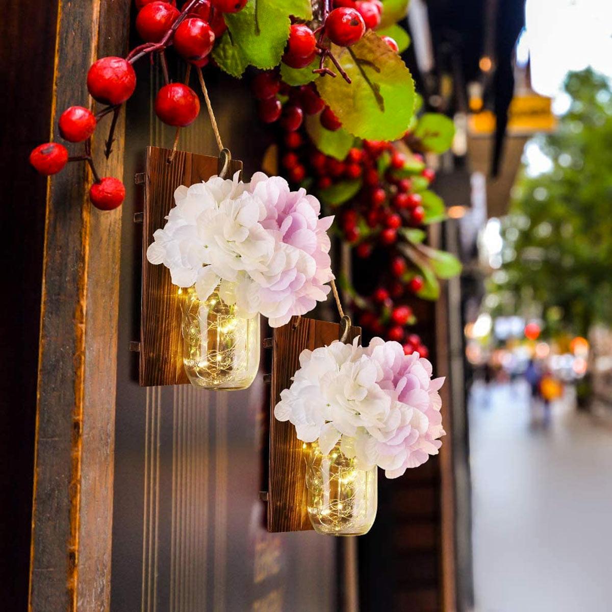 Decorazione fai da te da parete con pallet e barattoli di vetro.