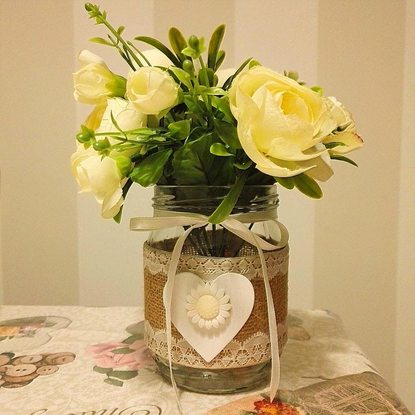 Vasetto con rose gialle realizzato con un vasetto di vetro riciclato.