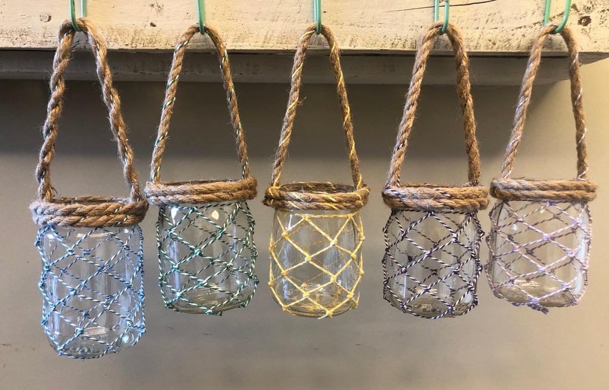 Barattoli di vetro riciclati diventano vasetti sospesi con corda.
