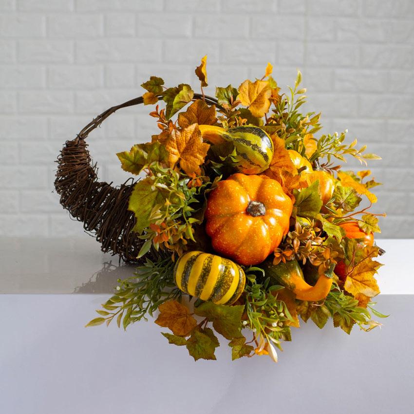Bellissimo centrotavola con rametti, zucche e foglie autunnali.