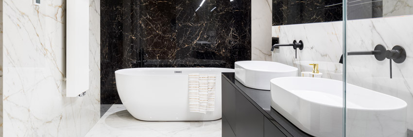 Bagno di design con vasca e parete in marmo nero.